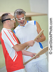 2 men chatting between two pelota games