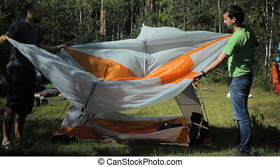2 men stacked orange tent. Summer sunny day in the forest
