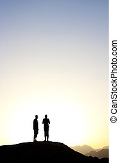 2 people standing on top of a mountain