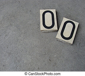 2 plastic 0 zero number on gray stone surface