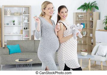 2 pregnant women holding teddy bear