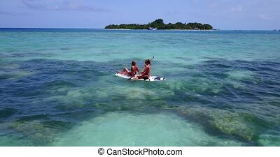 2 pretty young girls on a surfboard paddleboard with aerial...