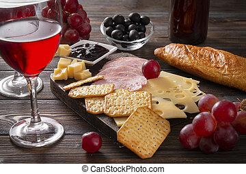 red wine glasses, slices of cheese , cracker, ham, olives, jam, grapes, baguette, bottle, corkscrew, on a dark wooden background, snack