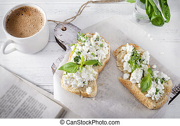 sandwiches with soft cheese and Basil, a Cup of black coffee, a book of herbs on a white wooden background, Breakfast,