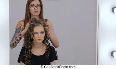 2 shots. Hairdresser finishing hairstyle for teen girl