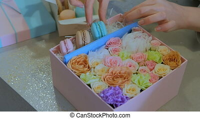 2 shots. Professional florist making gift box with flowers and cake macarons at flower shop