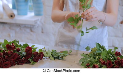 2 shots. Professional florist working with flowers at studio