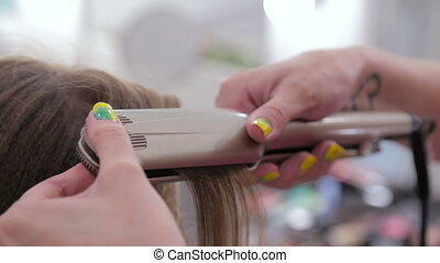 2 shots. Professional hairdresser doing hairstyle for young pretty woman with long hair