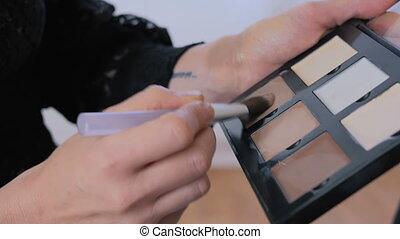 2 shots. Professional make-up artist applying makeup on woman's face