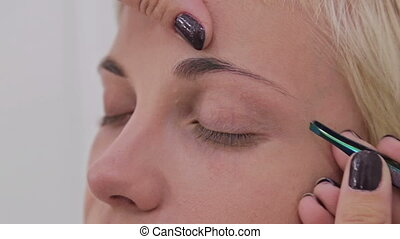 2 shots. Professional make-up artist plucking eyebrows of...
