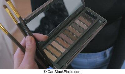 2 shots. Professional make-up artist applying eyeshadow - 2...