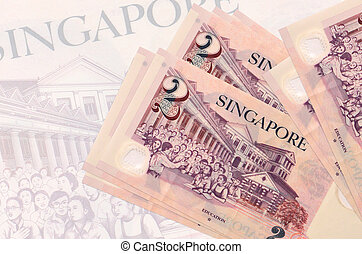 2 Singaporean dollars bills lies in stack on background of big semi-transparent banknote. Abstract presentation of national currency