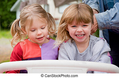 2 Toddler Girls Playing Outside in Toy Car