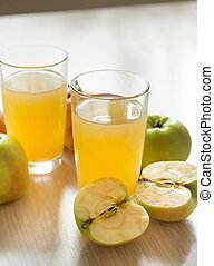 two glasses of apple juice, fresh apples on the table, fruit and fruit juice