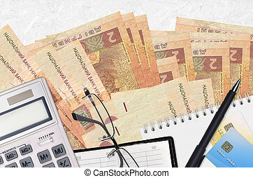 2 Ukrainian hryvnias bills and calculator with glasses and pen. Tax payment concept or investment solutions. Financial planning or accountant paperwork