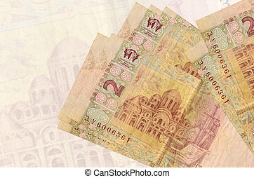 2 Ukrainian hryvnias bills lies in stack on background of big semi-transparent banknote. Abstract presentation of national currency