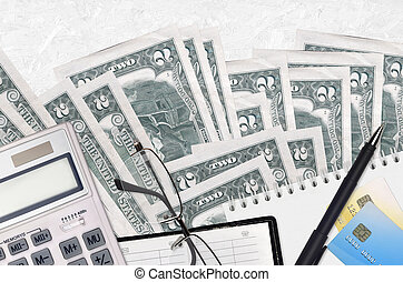 2 US dollars bills and calculator with glasses and pen. Tax payment concept or investment solutions. Financial planning or accountant paperwork