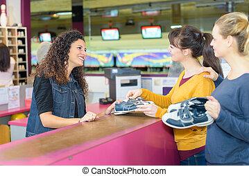 2 women borrowing bowling shoes