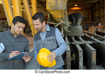 2 workers discussing in metalworks factory