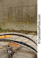 2 worn wheels laying on pavement sidewalk with wall