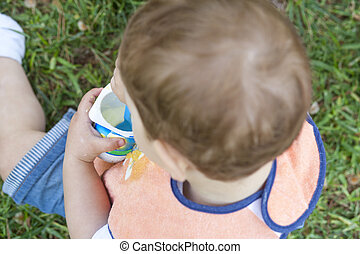2 year-old boy eating a yoghurt sitting on the grass