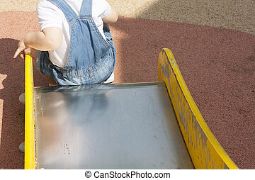 2 year-old boy playing on slider at playground