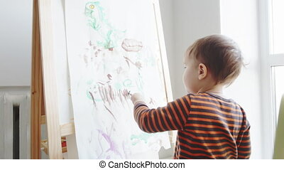 2 year-old child paints with watercolors