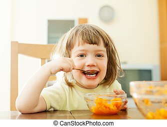 2 years child eats carrot salad with spoon in home