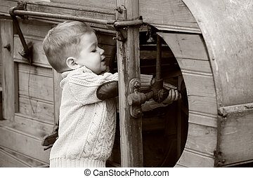 2 years old curious Baby boy managing with old agricultural Machinery on sepia brown color