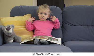 2 years old lovely baby girl sit on sofa read story book and show emotions.