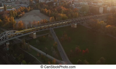 2 Yellow Subway Trains passing on Bridge above public park with Red and Orange Autumn colored trees in Sunset light, Aerial Wide Angle Establishing Shot