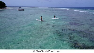 2 young teenage men surfboard paddleboard with aerial view...