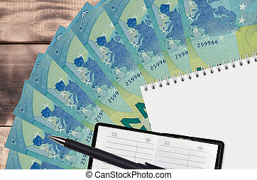 20 euro bills fan and notepad with contact book and black pen. Concept of financial planning and business strategy