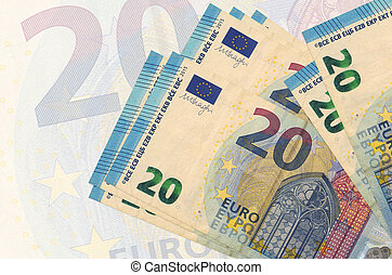 20 euro bills lies in stack on background of big semi-transparent banknote. Abstract presentation of national currency