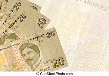 20 Turkish liras bills lies in stack on background of big semi-transparent banknote. Abstract business background with copy space