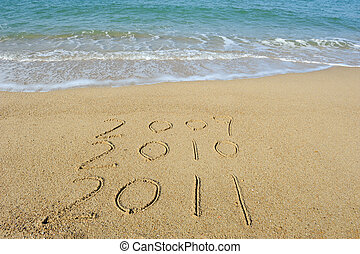 2011 year handwritten in sand on a beach