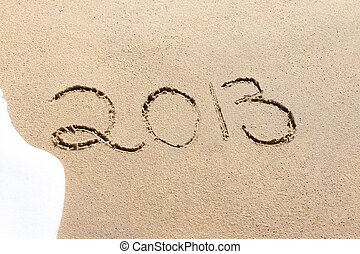 2013 written in the sand on a beach