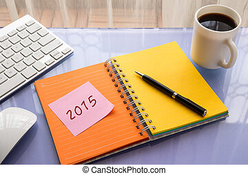 2015 year number on note pad stick on blank colorful paper notebook at office table, new year resolution concepts