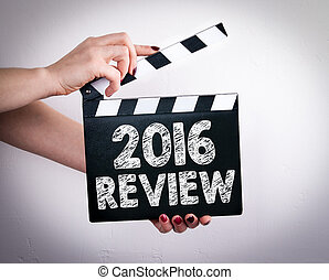 2016 Review concept. Female hands holding movie clapper