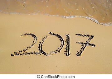 2017 written in sand, on tropical beach
