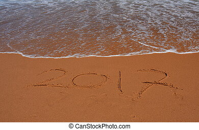 """2017 written on sand at sunset.  2017 lettering on the beach. """"2017"""" drawn on sand on a beach, closeup shot. 2017  written in sand, on tropical beach."""
