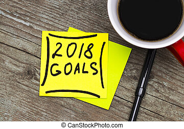 2018 goals - handwriting in black ink on a sticky note with a cup of coffee, New Year resolutions concept