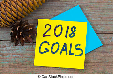 2018 goals - handwriting in black ink on a sticky note with a pine cones, New Year resolutions concept