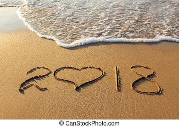 2018 new year written on sandy beach.