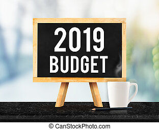2019 budget on blackboard with easel on black marble table with coffee cup and pencil on blurred office building hall way background, New year business plan concept.