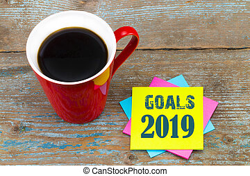 2019 goals - handwriting in black ink on a sticky note with a cup of coffee, New Year resolutions concept