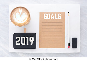 2019 goals on brown recycle paper with pencil, clip blackboard, pencil, eraser and coffee cup on white and grey marble table. mock up for adding text, new year resolution concept.