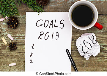 2019 goals on paper note book background and cup of coffee on wood table, business and new year concept
