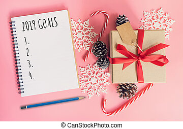 2019 Goals, top view brown gift box, notebook and christmas decoration for new year on pink pastel color.