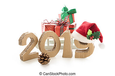 2019, handmade 3D numbers made of reused cardboard paper, with santa's red hat on nine and presents, on white background.